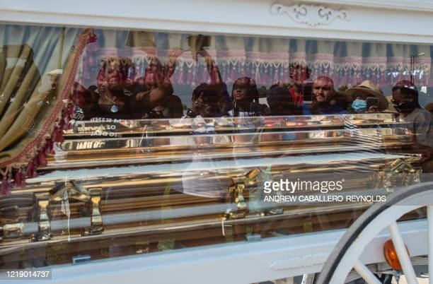 TOPSHOT Mourners are reflected as they watch the casket of George Floyd carried by a white horsedrawn carriage to his final resting place at the...