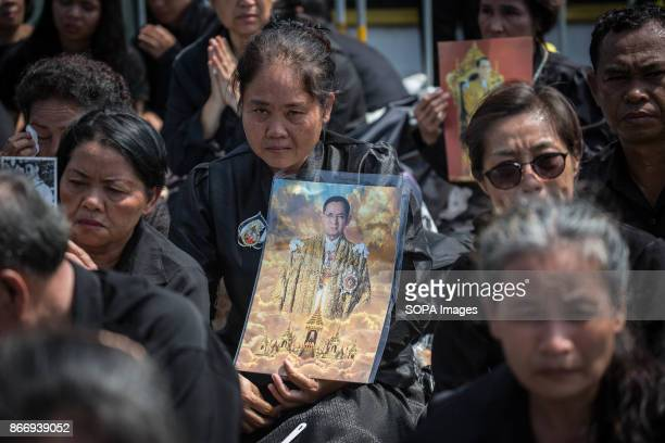 Mourners are seen crying while holding a portrait of King Rama 9 as they attend Thailand's Late King Bhumibol Adulyadej's ashes and relics to be...
