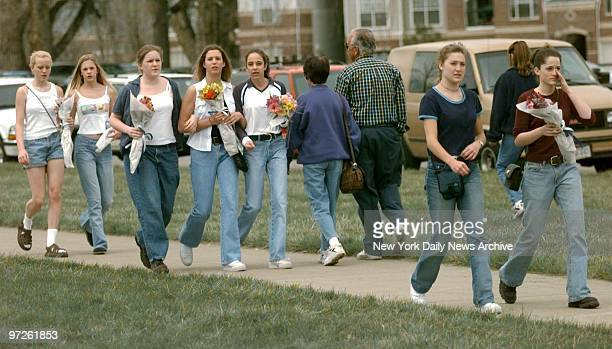 Mourners arrive with flowers at Columbine High School in Littleton Colo where two teenagers shot to death 12 students and a teacher before killing...