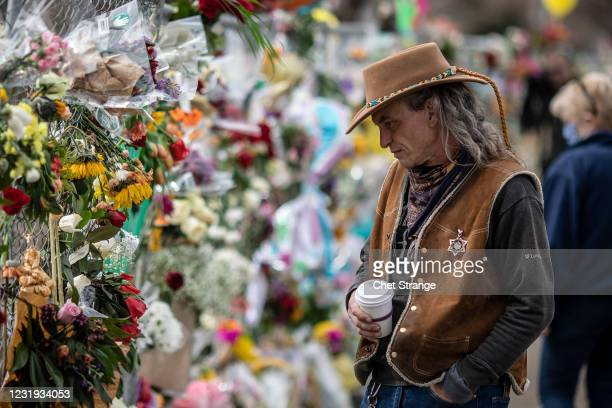 Mourners at a memorial set up outside the site of a shooting at a King Soopers grocery store on Thursday, March 25, 2021 in Boulder, Colorado. The...