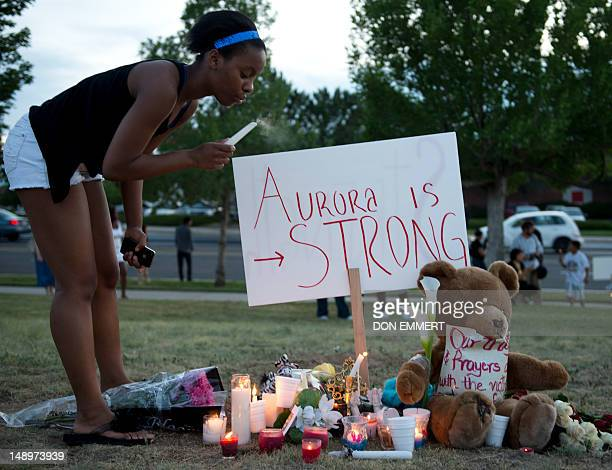 Mourners at a vigil blows out a candle near theater where 12 people were killed July 20 2012 in Aurora Colorado A graduate student who told police he...