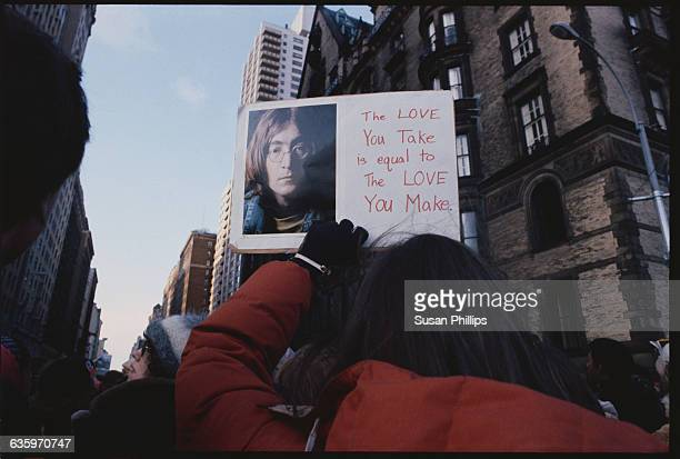Mourners at a vigil for John Lennon hold up a sign that reads 'The love you take is equal to the love you make' The crowd stands outside the Dakota...