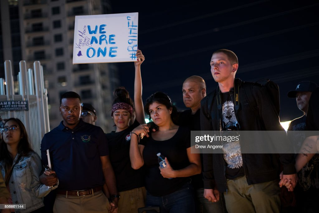 Mourners attend a candlelight vigil at the corner of Sahara Avenue and Las Vegas Boulevard for the victims of Sunday night's mass shooting, October 2, 2017 in Las Vegas, Nevada. Late Sunday night, a lone gunman killed more than 50 people and injured more than 500 people after he opened fire on a large crowd at the Route 91 Harvest Festival, a three-day country music festival. The massacre is one of the deadliest mass shooting events in U.S. history.