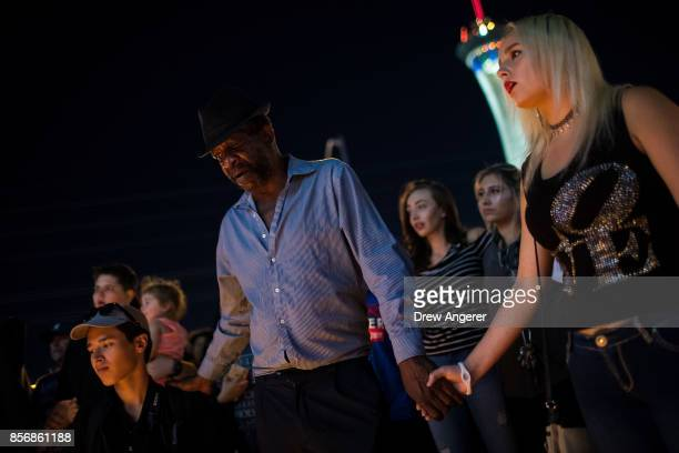 Mourners attend a candlelight vigil at the corner of Sahara Avenue and Las Vegas Boulevard for the victims of Sunday night's mass shooting October 2...