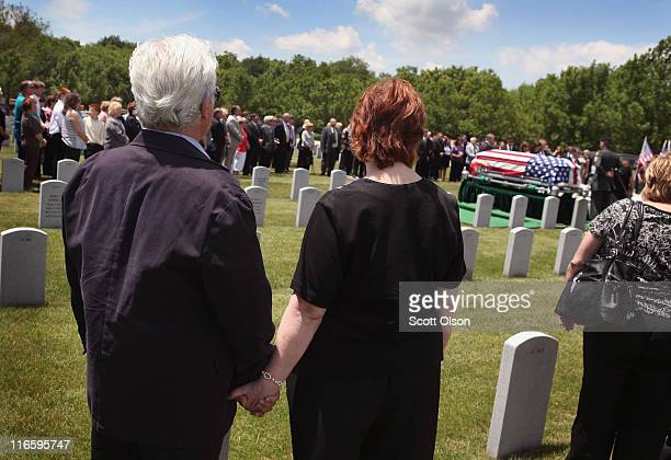 Mourners attend a service for US Army PFC Michael Olivieri of Homer Glen Illinois at Abraham Lincoln National Cemetery on June 16 2011 in Elwood...