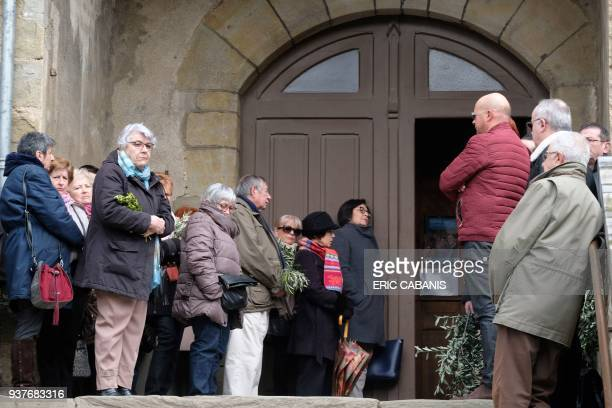 Mourners attend a service of remembrance from outside the Saint Etienne Church in Trebes in southwest France on March 25 two days after a man carried...