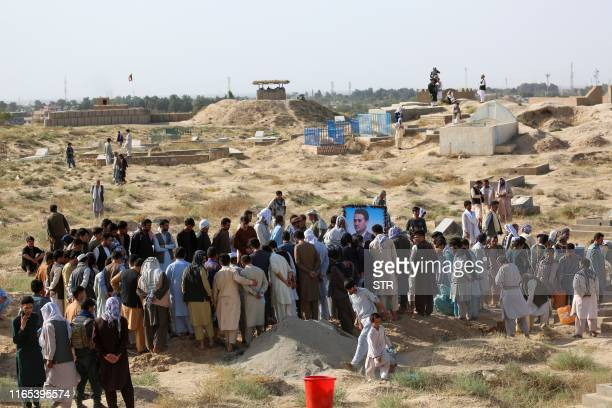 Mourners attend the burial ceremony of Kunduz police spokesman Sayed Sarwar Hussaini who was killed by a suicide bomber while he was speaking to...