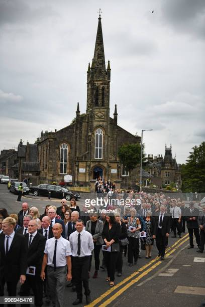 Mourners attend the funeral of Bay City Roller guitarist Alan Longmuir attends his funeral at Allan Church on July 12 2018 in Bannockburn Scotland...