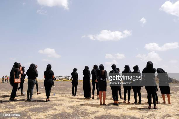 Mourners, believed to be Ethiopian Airlines cabin crew members, arrive to pay their respects at the crash site of Ethiopian Airlines Flight ET302 on...