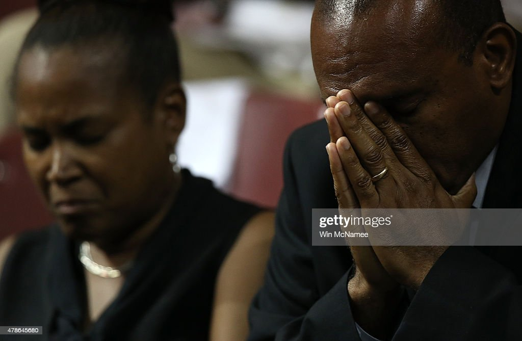 Mourners bow their heads in prayer during the funeral service where U.S. President Barack Obama delivered the eulogy for South Carolina State senator and Rev. Clementa Pinckney who was killed along with eight others in a mass shooting June 26, 2015 in Charleston, South Carolina. Suspected shooter Dylann Roof, 21 years old, is accused of killing nine people on June 17th during a prayer meeting at the Emanuel AME church in Charleston.