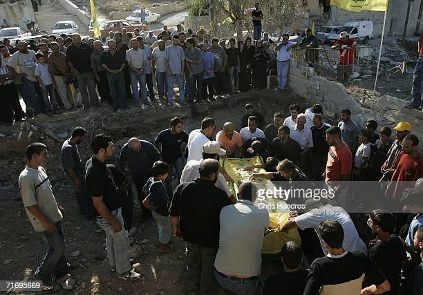 Mourners bring the body of Mohammed Samhat a Hezbollah fighter killed in a battle with Israeli forces to his gravesite during his funeral August 22...