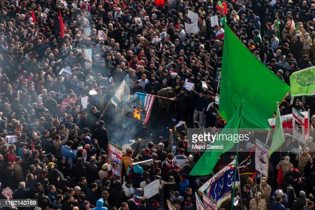 Mourners burn U.S. And Israeli flags during a funeral ceremony of Iranian Major General Qassem Soleimani and others who were killed in Iraq by a U.S....