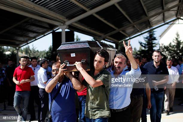 Mourners carry a coffin during a funeral ceremony for the victims of a suicide bomb attack yesterday which killed 32 people in the southern Turkish...