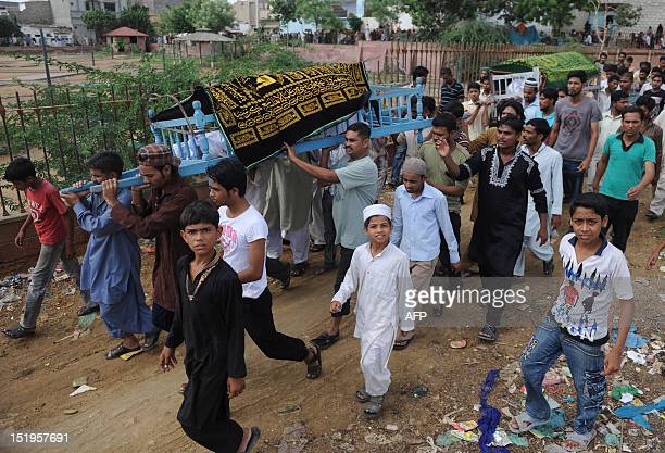 Mourners carry a coffin during a funeral for garment factory victims in Karachi on September 13 2012 Pakistan on September 13 registered murder...