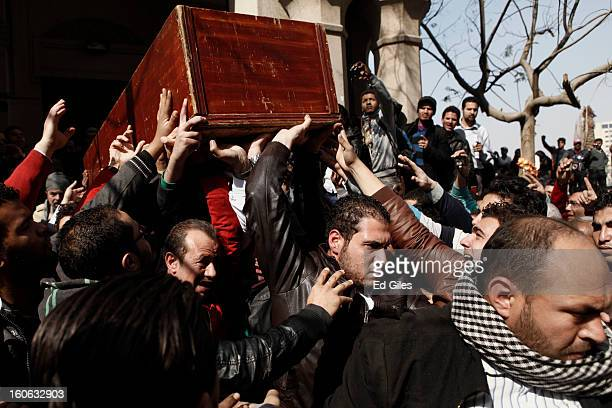 Mourners carry a coffin through the crowds at a funeral for two protesters killed during violent clashes with Egyptian security forces in the...