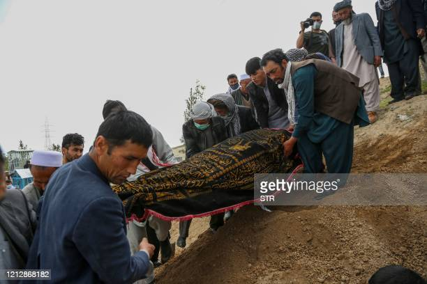 Mourners carry a covered dead body during a burial ceremony following a suicide attack in a maternity hospital at a cemetery in Kabul on May 13 2020...