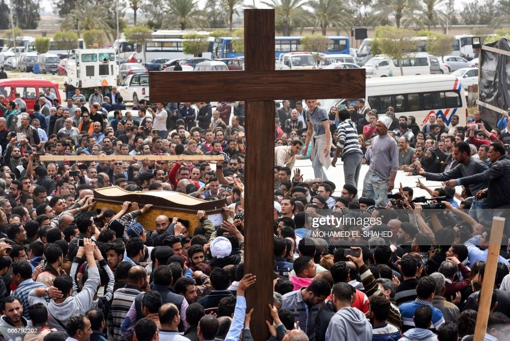 Mourners carry a large cross and the coffin of one of the victims of the blast at the Coptic Christian Saint Mark's church in Alexandria the previous day during a funeral procession at the Monastery of Marmina in the city of Borg El-Arab, east of Alexandria on April 10, 2017. Egypt prepared to impose a state of emergency after jihadist bombings killed dozens at two churches in the deadliest attacks in recent memory on the country's Coptic Christian minority. /