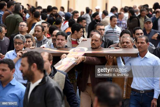 Mourners carry a large cross during a funeral procession on April 10 2017 at the Monastery of Marmina in the city of Borg ElArab for the victims of...
