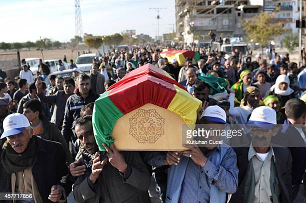 Mourners carry coffins during the funeral of Kurdish fighters, killed in clashes with IS militants in Kobani, Syria, at the cemetery in Suruc, on the...