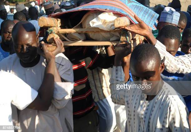 Mourners carry for burial the victims of suicide bomb attacks in the regional capital ofMaiduguri in northeast Nigeria on November 16 2017 Twelve...