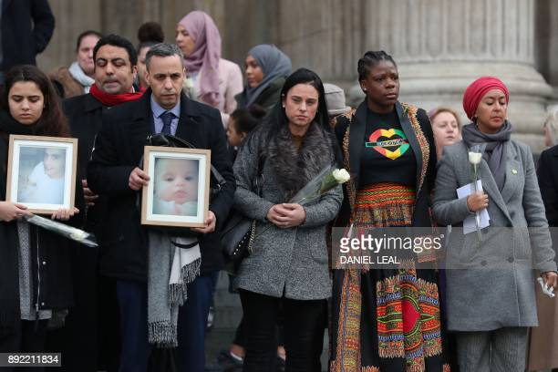 Mourners carry pictures of victims of the fire and white roses as they leave St Paul's cathedral after attending a Grenfell Tower National Memorial...
