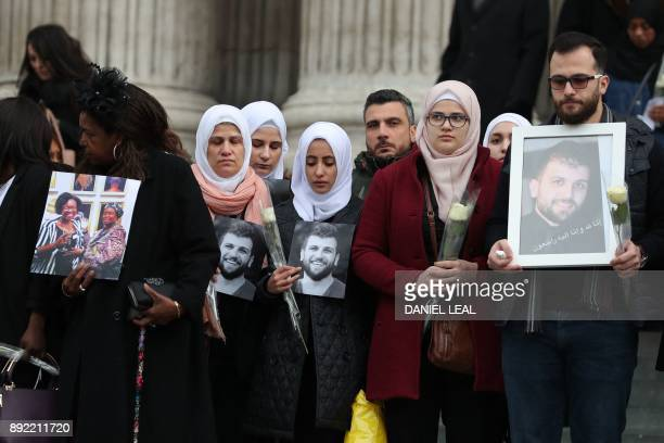 Mourners carry pictures of victims of the fire as they leave St Paul's cathedral after attending a Grenfell Tower National Memorial service on...