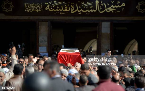Mourners carry the bier of the late popular singer and actress Shadia draped with an Egyptian flag during her funeral at the Sayeda Nafisa mosque in...