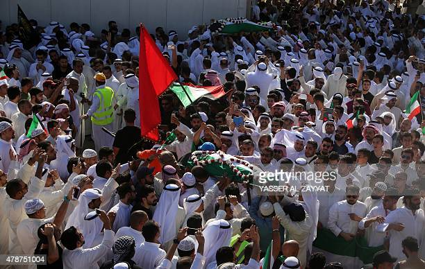 Mourners carry the bodies of two of the victims of the AlImam AlSadeq mosque bombing during a mass funeral at Jaafari cemetery in Kuwait City on June...