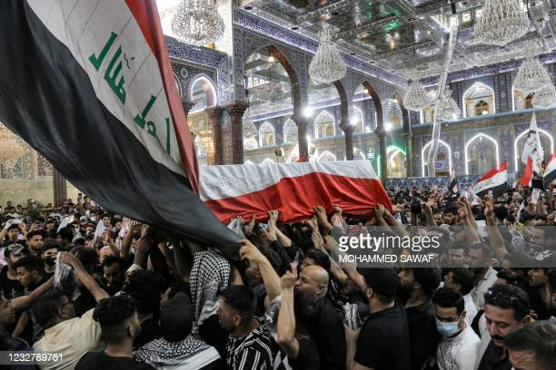 Mourners carry the body of Iraqi anti-government activist Ihab al-Wazni during his funeral at the Imam Hussein Shrine in the central holy shrine city...