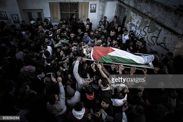 Mourners carry the body of Mahmoud Edwan a Palestinian who died overnight during an Israeli military operation on December 16 2014 during his funeral...