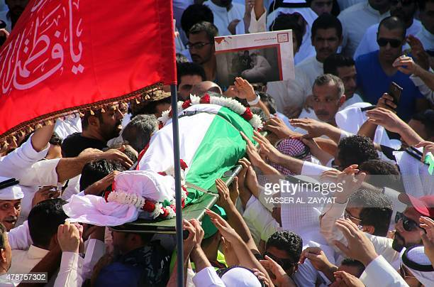 Mourners carry the body of one of the victims of the AlImam AlSadeq mosque bombing during a mass funeral at Jaafari cemetery in Kuwait City on June...