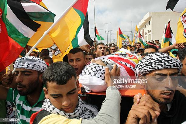 Mourners carry the body of Palestinian Amjad Hatem AlJundi during his funeral on October 10 2015 in the village of Yatta south the West Bank town of...