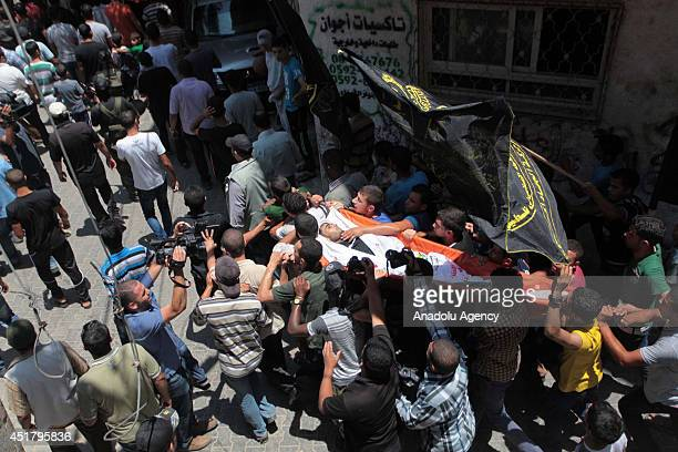 Mourners carry the body of Palestinian Marwan Sleem during his funeral in the central Gaza Strip July 7 2014 Israeli airstrikes aiming Gaza leave 9...