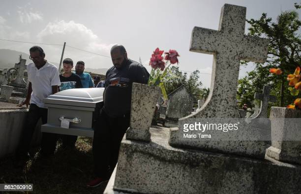 Mourners carry the casket of Wilfredo Torres Rivera who died October 13 after jumping off a bridge into a lake three weeks after Hurricane Maria on...