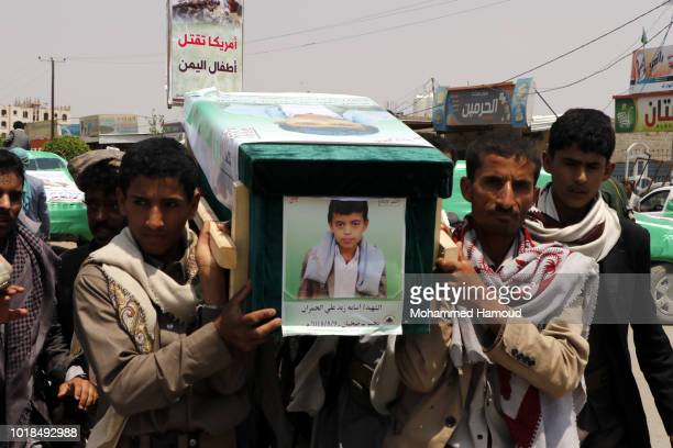 Mourners carry the coffin of a child at the funeral procession for those killed in an airstrike on a bus carried out last week by a warplane of the...