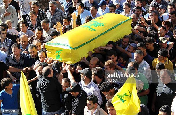 Mourners carry the coffin of a Lebanese Hezbollah fighter draped in the flag of the Lebanese Shiite Muslim party who was killed in Syria during his...