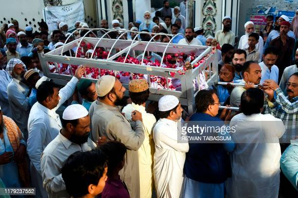 Mourners carry the coffin of a train fire victim during a funeral in Mirpurkhas on November 1 a day after a passenger train caught on fire in Rahim...