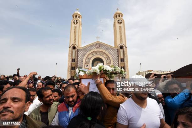 Mourners carry the coffin of a victim of the blast at the Coptic Christian Saint Mark's church in Alexandria the previous day during a funeral...