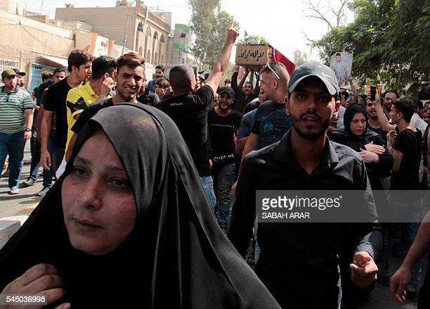 TOPSHOT Mourners carry the coffin of Akram alKarradi a 22yearold victim of a suicide bombing that ripped through Baghdad's busy shopping district of...