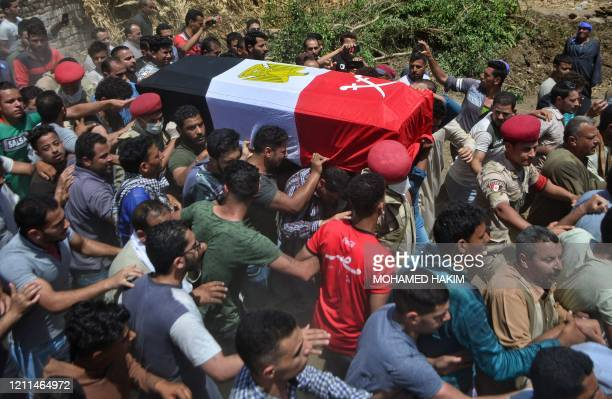 Mourners carry the coffin of Egyptian soldier Alaa Emad during his funeral in the village of Abwan in the Minya province on May 1 as his body was...