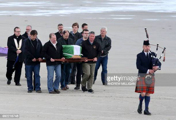 Mourners carry the coffin of Eilidh MacLeod which is draped with the Barra flag across Traigh Mhor beach on Barra island in the Outer Hebrides of...