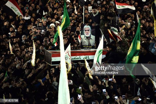 Mourners carry the coffin of slain Iraqi paramilitary chief Abu Mahdi alMuhandis toward the Imam Ali Shrine in the shrine city of Najaf in central...