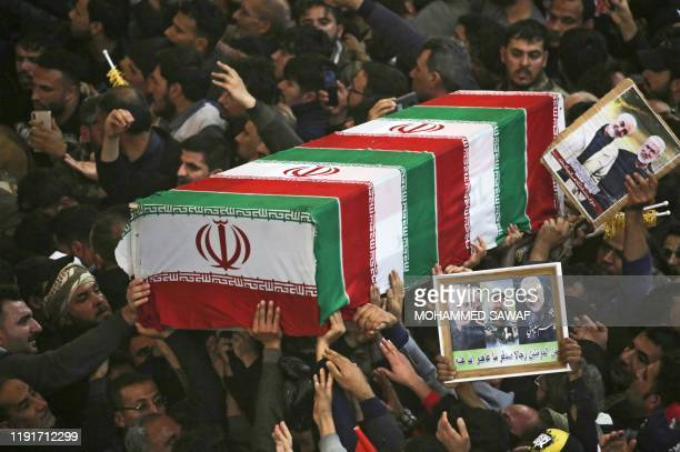 TOPSHOT Mourners carry the coffins of slain Iraqi paramilitary chief Abu Mahdi alMuhandis Iranian military commander Qasem Soleimani and eight others...