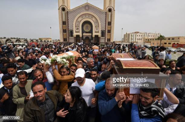Mourners carry the coffins of victims of the blast at the Coptic Christian Saint Mark's church in Alexandria the previous day during a funeral...