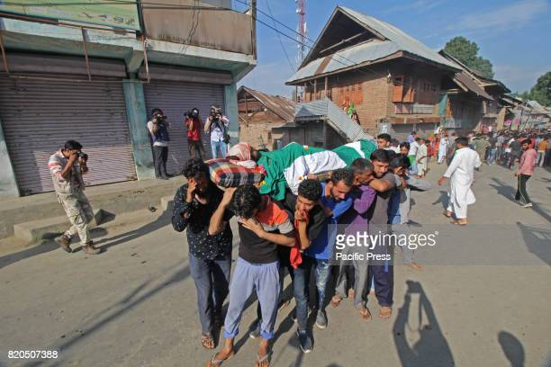 Mourners carry the dead body of Kashmiri man Tanveer Ahmad a tailor by profession after they suffered a teargas attack during his funeral in Beerwah...