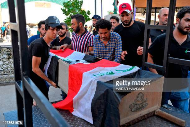 Mourners carry the Iraqi flag-draped coffin of a protester, who was killed amidst clashes in a demonstration, during his funeral in the central Iraqi...