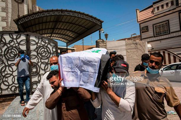 Mourners carry the Iraqi-flag draped coffin of slain activist Riham Yaaqub during her funeral in the centre of Iraq's southern city of Basra on...