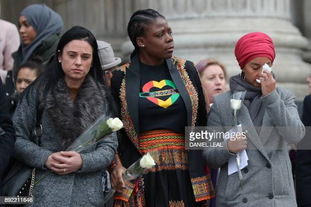 Mourners carry white roses as they leave St Paul's cathedral after attending a Grenfell Tower National Memorial service on December 14 2017 in...