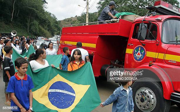 Mourners carrying the Brazilian flag, follow the casket of Jean Charles de Menezes as its being taken in a fire truck to Gonzaga, 600 km from Belo...