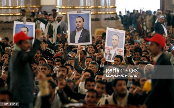 Mourners chant slogans and raise the portrait of slain Huthi leader Saleh alSamad and his six body guards during his funeral at a mosque in the...